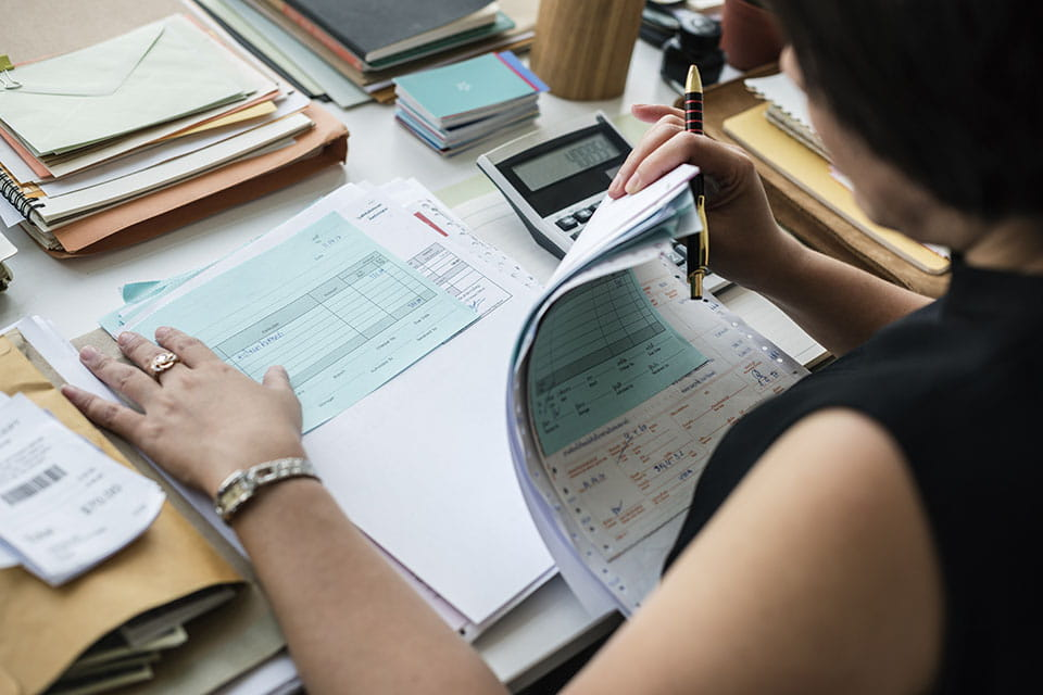 employee sitting at desk with forms and papers and a calculator holding a ballpoint pen