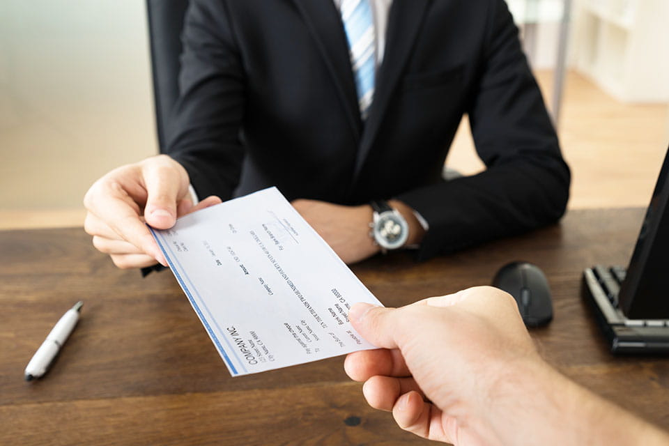 employee sitting at a desk handing a check form to an employee