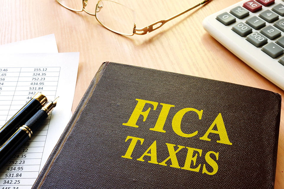 fica taxes note book, fountain pen, glasses, calculator, and papers on a wooden desk
